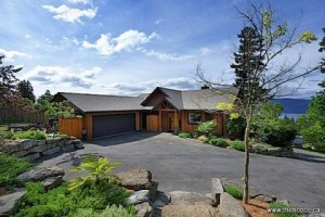 Coastal Craftsman: A gentle curve in the paved driveway leads to a level access entry court. Stone walled gardens flank the modern craftsman home.